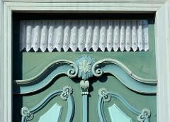 Detail einer Schmucktür in Bleckede - aufgesetzte Leisten mit Schnitzerei - geklöppelte Gardinen im Oberfenster.
