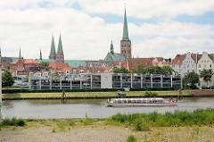 Blick über die Kanaltrave von Lübeck - Parkhaus am Kanalufer, Kirchtürme der Stadt - ein Ausflugsschiff mit Touristen an Bord auf der Rundfahrt durch die Kanäle der Stadt.
