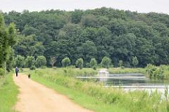 Elbe-Lübeck-Kanal, bewaldete Hügel - Spaziergänger mit Hund auf dem ehem. Treidelpfad, jetzt Fahrradroute Alte Salzstraße / ein Motorboot fährt Richtung Lauenburg.