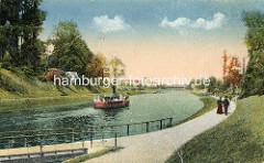 Historische Ansicht vom Travekanal in Lübeck - ein Ausflugsschiff dampft auf dem Wasser - Spaziergänger auf der Promenade.