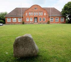 Altes Schulgebäude von Sülfeld, erbaut 1913 - im Vordergrund ein Findling mit der Inschrift Up ewig ungedeelt.