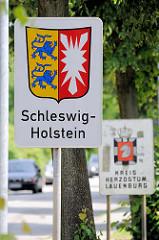 Schild Landesgrenze Schleswig-Holstein /  Wappen. Das Schleswig-Holsteiner Wappen vereint die Symbole der beiden ehemaligen Herzogtümer Schleswig und Holstein: Zwei rot bewehrte Löwen auf goldenem Grund und ein silbernes Nesselblatt auf rotem Grund.