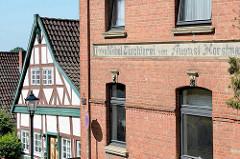 Werkstattgebäude - Backsteinarchitektur, Bau & Möbeltischlerei, daneben ein Fachwerkhaus mit grün gestrichenen Balken - Architekturbilder aus Lauenburg / Elbe.
