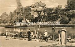 Travekanal in Lübeck - Ruderbootverleih am Kanalufer - ein Dampfschiff fährt qualmend unter Dampf Richtung Trave - am Ufer das Gebäude der Lübecker Navigationsschule / Seefahrtschule.