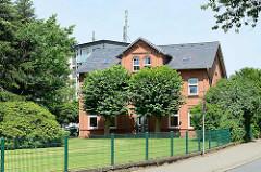Einstöckiges Backsteingebäude - zwei Linden symmetrisch am Eingang - Rasen und Metallzaun; im Hintergrund Wohnblock der 1970er Jahre / Architekturbilder aus Wentorf bei Hamburg.