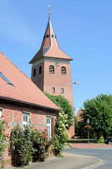 Kirchturm der St. Jacobikirche in Bleckede - im Vordergrund ein Fachwerkhaus mit blühenden Stockrosen.