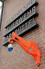 Freiwillige Feuerwehr Barsbüttel, Schrift auf der Fassade; roter Hahn mit Blaulicht.