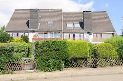 Einstöckige Doppelhäuser mit vier Wohneinheiten und gemeinsamen Schornsteine - unterschiedliche Heckengestaltung.