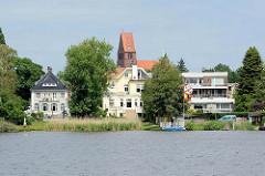 Blick über die Wakenitz zur St. Gertrud Kirche in Lübeck - am Ufer Wohnhäuser / Villen.