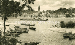 Historische Ansicht - Ruderboote / Fischerboote im natürlichen Hafen bei Hohnstorf an der Elbe, ein Binnenschiff fährt elbaufwärts. Altstadt von Lauenburg und Kirchturm der Maria Magdalenen Kirche.