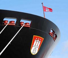 """Seil und Schiffsbug des Containerschiffs """"Hanover"""" am Hamburger Container Terminal Altenwerder; über dem Hamburg Wappen flattert die Hamburg Fahne im Wind."""