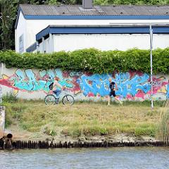 Mauer mit Graffiti am Kanalufer der Kanaltrave - Fahrradfahrer und Jogger.
