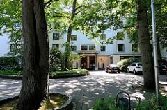 Eingangsbereich vom Privathotel Lindtner in Hamburg Heimfeld - Parkplatz, hohe Bäume.