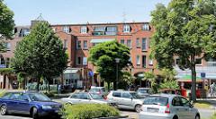 Geschäfts- und Wohnhaus, Neubau der 2000er Jahre - parkende und fahrende Autos / Straßenverkehr Hauptstraße in Wentorf.