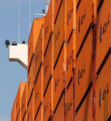 """Auf dem Containerschiff """" Hanover """" am Ballinkai des Terminals Hamburg Altenwerder sind die Container an Deck hoch gestapelt - ein Schiffsoffizier in Uniform blickt vom Ausguck zum Kai."""