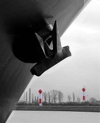 """Der Schiffsanker vom Containertransporter """"Hanover"""" - im Hintergrund die Richtfeuer / Leuchtfeuer beim Altenwerder Containerterminal."""