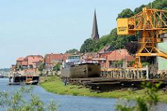 Werft an der Elbe / Lauenburg; ein Binnenschiff liegt zur Reparatur auf der Slipanlage / Helge, Werftkran - im Hintergrund Häuser und Kirchturm der Stadt.
