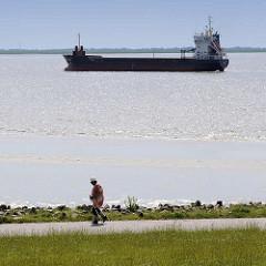 Blick vom Elbdeich bei Brunsbüttel - ein Tankschiff fährt Richtung Schleuse; eine Nordic Walkerin walkt am Ufer der Elbe.