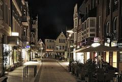 Die Bergedorfer Fussgängerzone Sachsentor als Nachtaufnahme; die Geschäfte und Hausfassaden sind beleuchtet, vereinzelt gehen Passanten durch Hamburg bei Nacht.