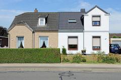 Doppelhaus mit unterschiedlicher Fassadengestaltung - Klinker und weisse Putzfassade, Hecke oder Zaun; Architektur in Brunsbüttel, Kreis Dithmarschen.