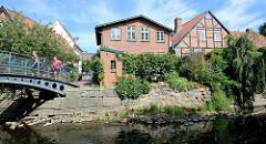 Fussgängerbrücke über die Trave - Wohnhäuser am Wasser, Heiligengeiststraße in Bad Oldesloe.