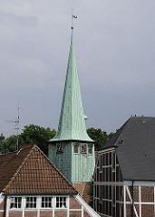 Zwischen den Fachwerkhäusern ragt der Kirchturm der St. Petri und Pauli Kirche empor - dahinter sind die Bäume des Schlossparks vom Bergedorfer Schloss zu erkennen.