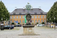 Blick über den Marktplatz zum Gebäude vom Schloss Oranienbaum; im Vordergrund ein stilisierter Orangenbaum.