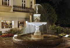 Abends wird der Springbrunnen auf dem Kaiser Wilhelm Platz beleuchtet. Die zwei Wasserbecken aus Gusseisen und die einzelnen Dekorelemente der Wasseranlage sind farblich gefasst.