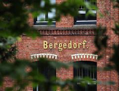 An dem historischen Industriegebäude ist in goldenen Buchstaben der Name Bergedorfs zu erkennen. Über den Fenstern wird mit hellen Steinen ein Dekor erstellt, dass sich von der roten Backsteinfront abhebt.