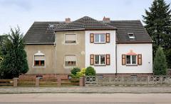 Architektur in Oranienbaum - Doppelhaus mit unterschiedlicher Fassadengestaltung - grauer Putz und weisse Hausfassade mit Fensterluken.