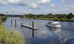 Der ehemalige Binnenhafenschlepper OMKA (hier ohne Mast)  auf einer Chartertour mit Gästen bei der Einfahrt in den Bergedorfer Schleusengraben. Der 1926 auf einer Hamburger Werft gebaute Schlepper hat bis 1990 in der DDR seinen Dienst getan.