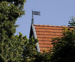 Eine Wetterfahne mit der Jahreszahl 1896, dem Baujahr des Gebäudes, ziert das Dach des Hauses im Villenviertel von Hamburg Bergedorf. Ende des 19.  Jahrhunderts wurde begonnen, das sogenannte Villenviertel zu bebauen -  wohlhabende Hamburger und