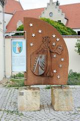 Wappen von Coswig / Anhalt als Metallarbeit, daneben Schild mit Beschreibung: In einem blauen mit 12 goldenen Sternen bestreuten Schild steht eine golden gekrönte Frauengestalt.