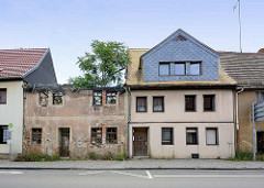 Wohnhäuser in der Lutherstadt Eisleben; neu + alt - restauriert und bewohnt / verfallen mit großem Baum im Dach.