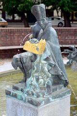 Marktbrunnen am Marktplatz von Aken / Elbe; Figurengruppe Erzbischof von Magdeburg - Sockelumschrift: Der Magdeburger Erzbischof beglückte unsere Gemeinde im Jahre des Herren 1270 mit einem Chorherrenstift.