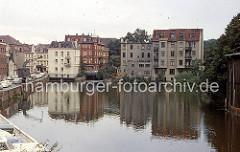 Blick in den Bergedorfer Hafen um 1970; auf der Kaimauer stehen neben dem Drehkran Kraftfahrzeuge - das gesamte Hafenufer wird als Parkplatz genutzt.