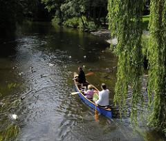 Tief hängen die Zweige der Weide über das Wasser der Bille beim Gewerkschaftsweg im Hamburger Stadtteil Bergedorf. Ein Kanu hat gerade auf seiner Tour mit seinen Fahrern die Brücke passiert und fährt flussabwärts. Enten schwimmen auf dem Wasser u