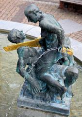 Marktbrunnen am Marktplatz von Aken / Elbe; Figurengruppe Symbol für die Zeit; Sockelinschrift: Die Zeit machte tiefe Einschnitte in unsere Stadt-vom Stadtbrand bis zur Treuhand - doch Bürgerfleiß schloss die Wunden wieder.
