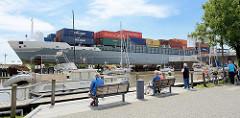 Das Containerschiff Jork verlässt die Schleuse in Brunsbüttel und fährt in den Nord-Ostsee-Kanal ein. Der Containerfeeder hat eine Länge von 134 m und eine Breite von 23 m; der Frachter hat eine Tragfähigkeit von 11 385 t und wurde 2001 auf der Sieta