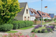 Wohnhäuser / Doppelhäuser mit Solaranlage auf dem Dach - blühende Blumen im Straßenbeet - Bilder aus Brunsbüttel, Kreis Dithmarschen.