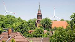 Dächer und Kirchturm der Jacobuskirche von Alt-Brunsbüttel - Rotoren von Windenergieanlagen.