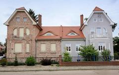 Doppelvilla in Oranienbaum - unterschiedliche Restaurierung, Fassadengestaltung und Vorgartenzaun.