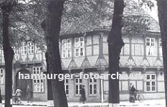 historische Aufnahme von alten Gasthof Stadt Hamburg ca. 1936 - hohe Linden stehen an der Strasse, Passanten gehen auf dem Bürgersteig oder schieben ihr Fahrrad vor dem Fachwerkgebäude. Das ca. 1550 errichtete Gasthaus hat aufwändige Schnitzerein