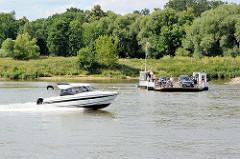 Ein Motorboot in schneller Gleitfahrt passiert die Gierfähre auf der Elbe bei Aken.