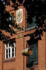 Historisches Speichergebäude einer Weinhandlung in Hamburg Bergedorf. Über der Inschrift ist ein Wappen eingelassen; vor einer der Speichertüren hängt an Seil und Haken einer Dachwinde ein Weinfass als Dekoration.