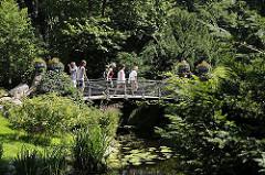 Der Wassergraben vom Bergedorfer Schloss wird mit dem Wasser der Bille gespeist. Bergedorf Besucher gehen über die historische Brücke über den Schlossgraben in den Schlosspark. Ein Fotograf fotografiert die eisernen Blumenkübel die an den Brücken