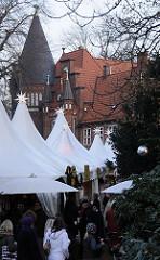 dicht gedrängt stehen die Stände auf dem Bergedorfer Weihnachtsmarkt - beleuchtete Sterne schmücken die Verkaufsstände, im Hintergrund die Dächer und Türme vom historischen Schlossgebäude.