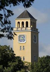 Der Turm vom Rathaus in Hamburg Bergedorf ragt zwischen den Bäumen empor - das Ziffernblatt der Turmuhr liegt auf blauem Grund mit goldener Zeiteinteilung; die Fassade vom Rathaus ist in einem zarten Ockergelb gehalten.