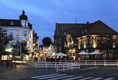 """Blick von der Alten Holstenstrasse in die Strasse Sachsentor der City Bergedorfs - die Geschäfte sind in der Abenddämmerung zur """"Blauen Stunde"""" beleuchtet. Rechts das historische Fachwerkgebäude vom Gasthaus """"Stadt Hamburg"""", das um 1550 gegründet"""