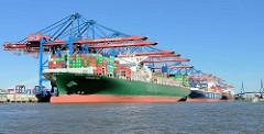 Blick über den Waltershofer Hafen zum Hamburger Container Terminal Burchardkai - drei Frachter liegen unter den Containerbrücken und werden beladen / entladen. Im Vordergrund das Frachtschiff  Thalassa Axia, dahinter die  CMA CGM Aquila.